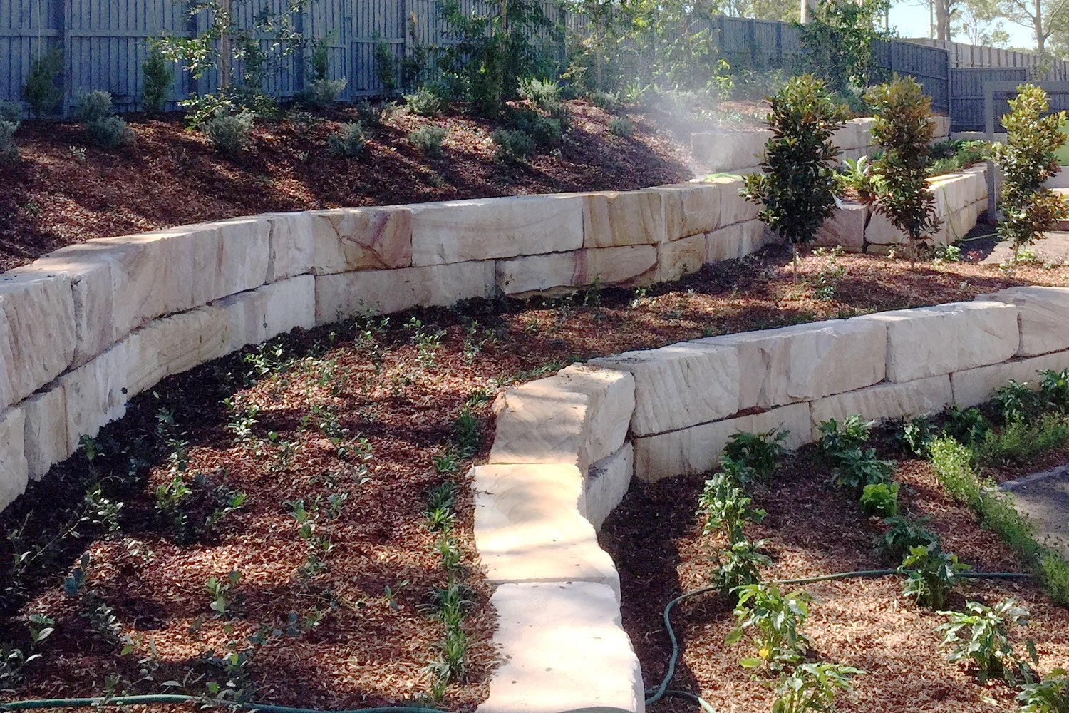 A sandstone log retaining wall built by Novascape Landscaping