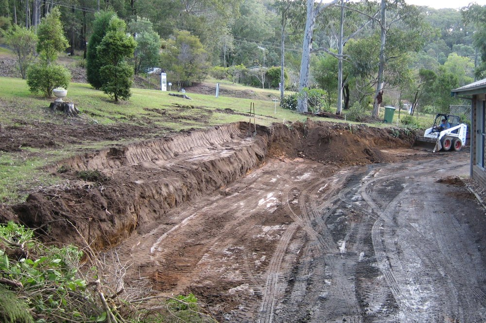 Excavation is often required to create a solid foundation for a retaining wall