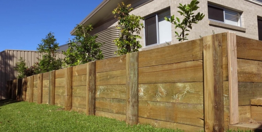 A treated pine post and rail retaining wall
